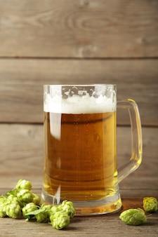 Стакан свежего пива с зеленым хмелем на сером фоне. вертикальное фото