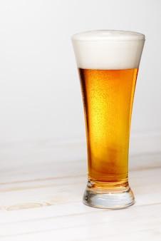 素朴な板の木製テーブルと新鮮なビールのガラス