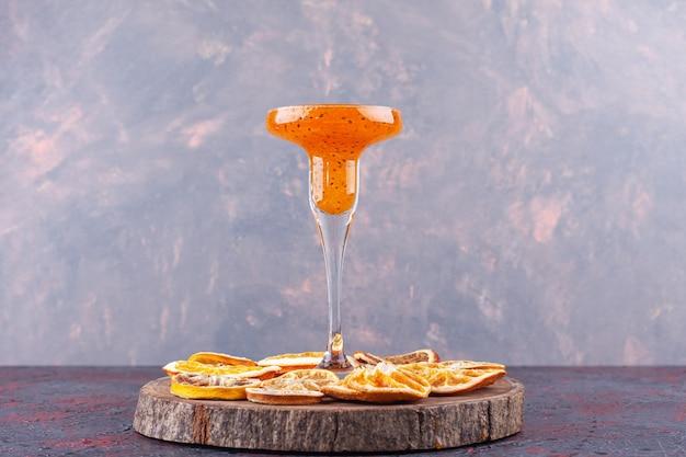 Стакан свежего коктейля и сушеных цитрусовых на деревянной доске.