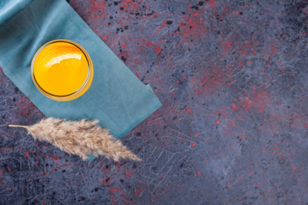 Стакан свежего коктейля с долькой апельсина на мраморе.