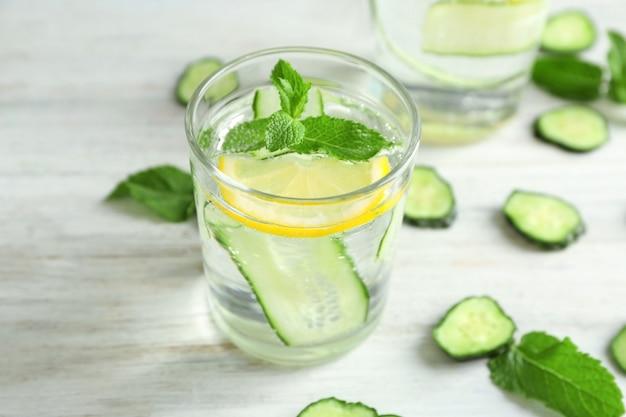 Стакан свежей огуречной воды с лимоном и мятой на столе