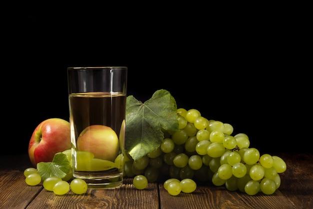 緑の背景のテーブルに新鮮なフルーツジュース、甘い緑のブドウとリンゴの束のガラス。