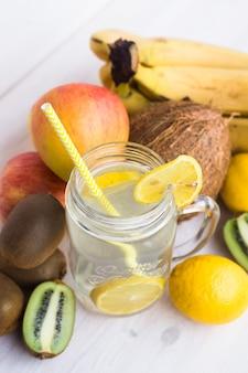 Стакан свежего лимонада в окружении фруктов