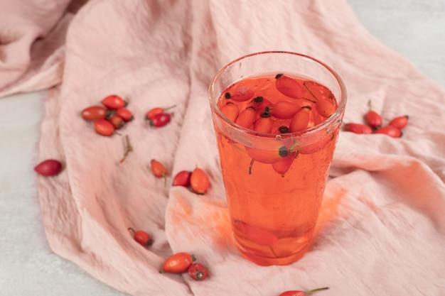 布にローズヒップと新鮮なレモネードのガラス