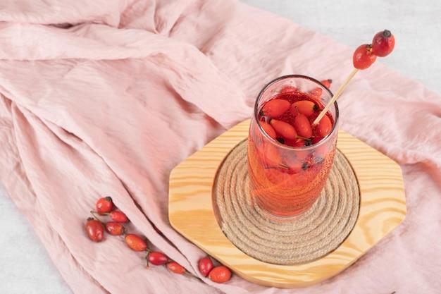 木製プレートにローズヒップと新鮮なレモネードのガラス
