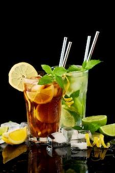 Стакан свежего ледяного чая лонг-айленд и коктейль мохито на черном фоне