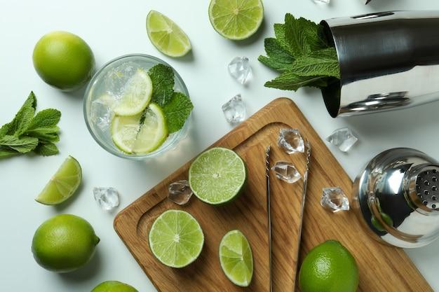 Стакан свежего коктейля мохито и ингредиенты на белом фоне