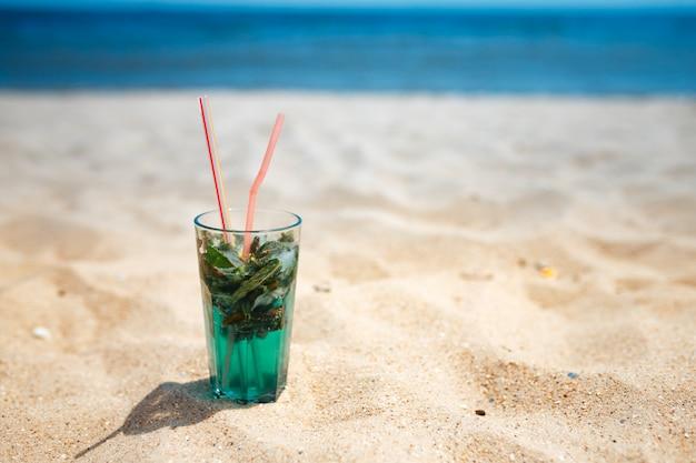 ビーチで新鮮なモヒートカクテルのグラス