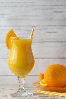 軽い木製の背景に新鮮なオレンジジュースのガラス。側面図。コピースペース付き