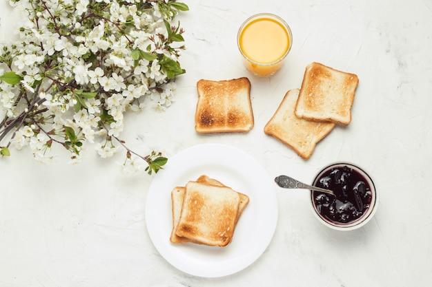 Стакан свежего апельсинового сока, тост, джем и весенние цветы на светлом фоне камень. концепция здорового завтрака. плоская планировка, вид сверху