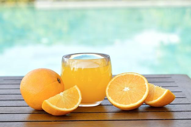 木製のテーブルに新鮮な果物と新鮮なオレンジジュースのガラス