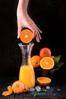 Стакан свежего апельсинового сока со свежими фруктами на деревянном столе