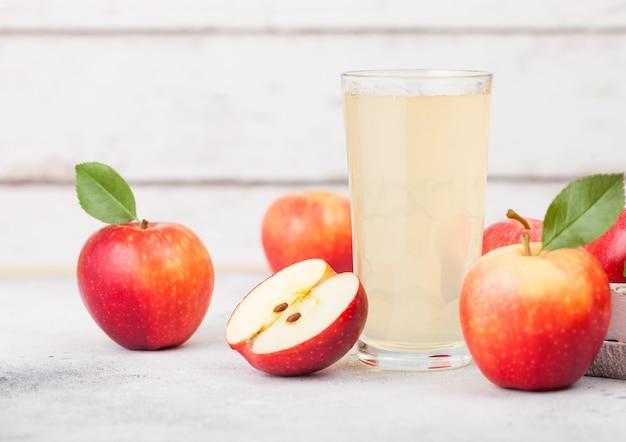 白い木製の背景にブレイバーンピンクの女性のリンゴと新鮮な有機リンゴジュースのガラス Premium写真