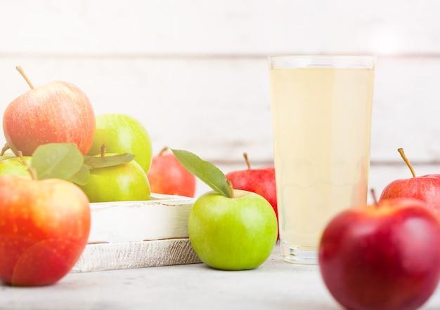 白い木製の背景にブレイバーンピンクの女性のリンゴと新鮮な有機リンゴジュースのガラス