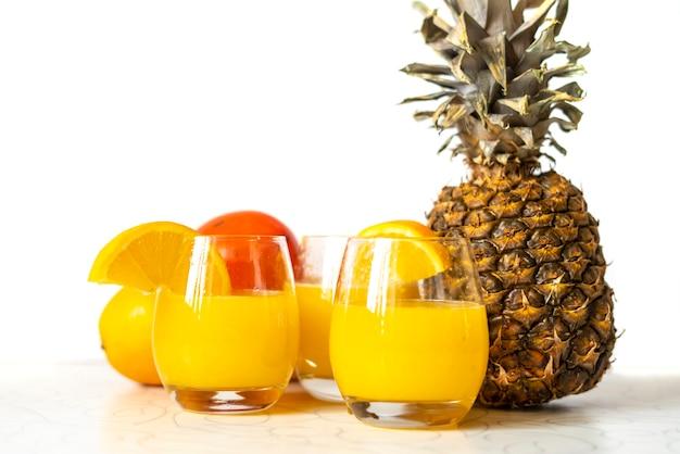 分離された木製のテーブルに新鮮なパイナップルとオレンジ色のスムージーのガラスb