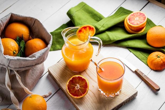 木製のテーブルに新鮮な押されたオレンジジュースとブラッドオレンジのガラス。明るい夏の気分。上面図