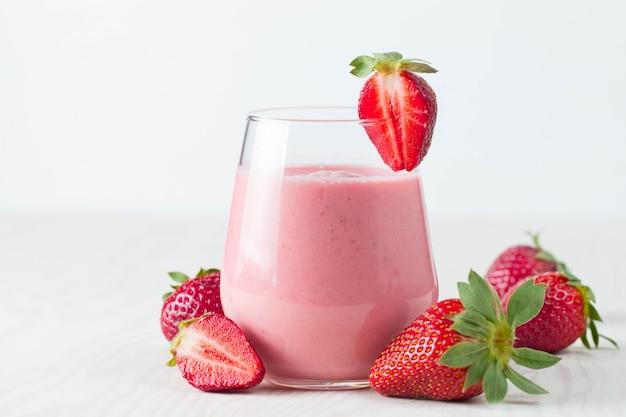 Стакан свежего клубничного молочного коктейля, коктейль и свежей клубники на розовый, белый и деревянный фон. здоровая еда и напитки концепции.