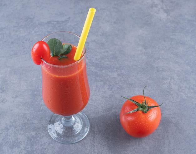 Стакан свежего томатного сока и помидор на сером фоне.