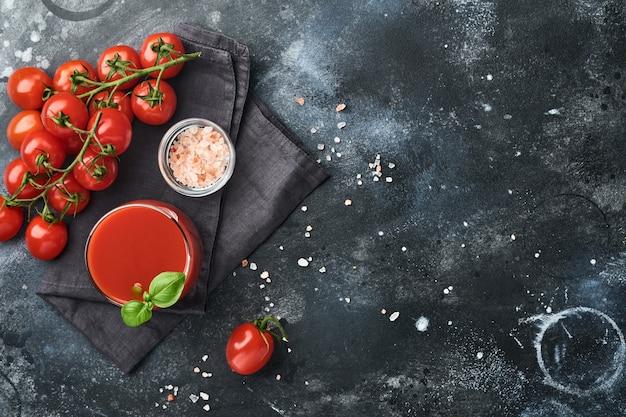 古い黒い背景の上の黒いプレートに新鮮なトマトジュース、塩、バジル、トマトのガラス。コピースペースのある上面図。