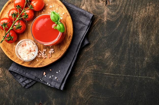 Стакан свежего томатного сока, соли, базилика и помидоров на деревянной подставке на старом деревянном фоне. с копией пространства.