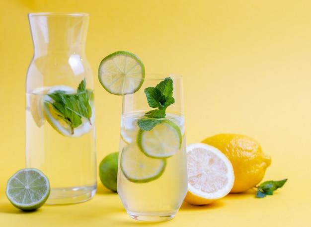 ライム スライスとミントの入った新鮮な水のガラスは、黄色の背景に残します。