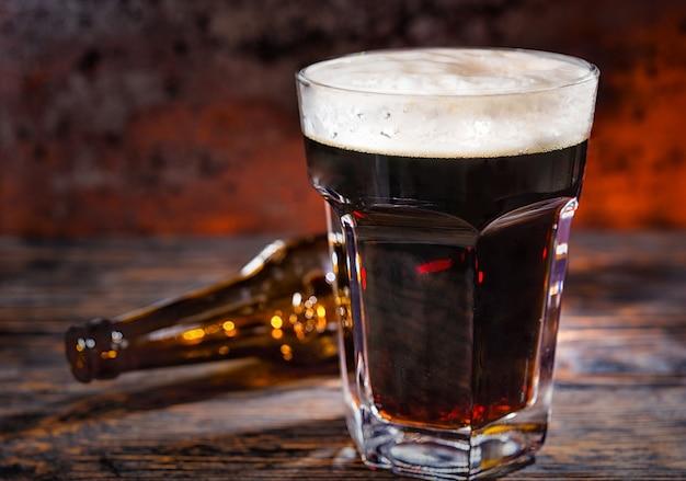 暗い木製の机の上の空のボトルの近くに注ぎたてのダークビールのグラス。食品および飲料の概念