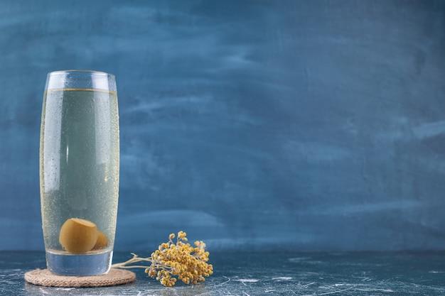 大理石の背景にフェイジョアフルーツとフルーツジュースのガラス。