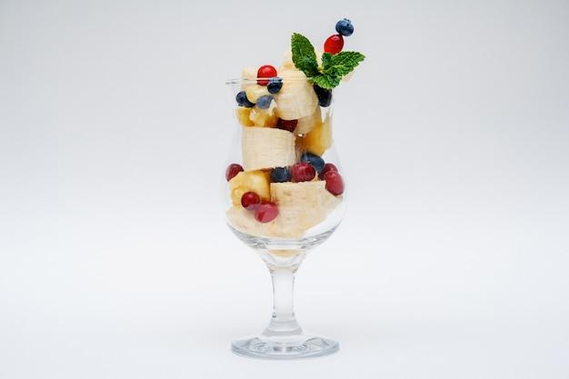 白い背景で隔離のフルーツサラダのガラス。