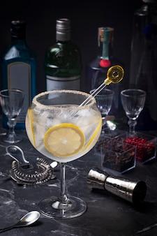 バーカウンターの黄色いドリンクミキサーでレモンのスライスが入ったジントニックのグラス、背景の飲用ボトルがぼやけている