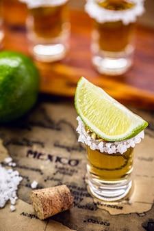 表面に古いメキシコの地図と金のテキーラのガラス