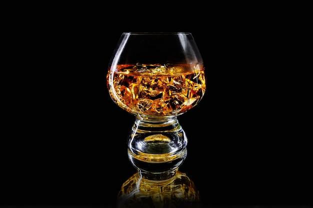 검은 반사 표면에 얼음 조각이 있는 황금 알코올 한 잔. 위스키 또는 코냑.