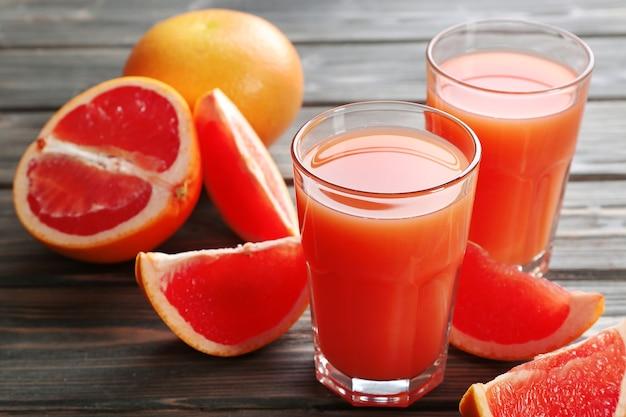 Стакан грейпфрутового сока и свежих фруктов на деревянном столе