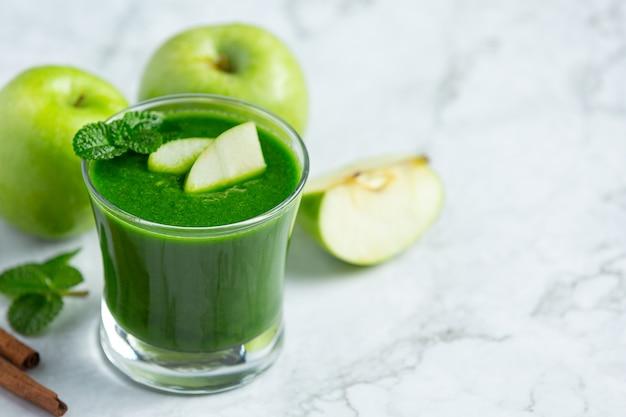 新鮮な青リンゴの隣に置かれた青リンゴの健康的なスムージーのガラス