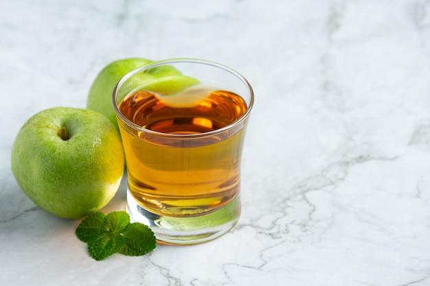 新鮮な青リンゴの隣に置かれた青リンゴの健康的なお茶のガラス