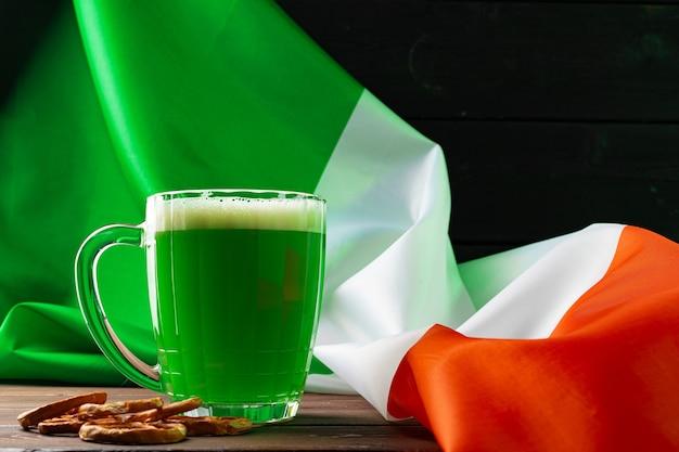 アイルランドの旗に対して緑色のビールのグラスをクローズアップ