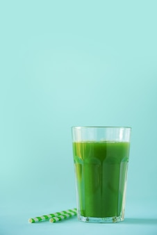 파란색 배경에 녹색 셀러리 스무디의 유리