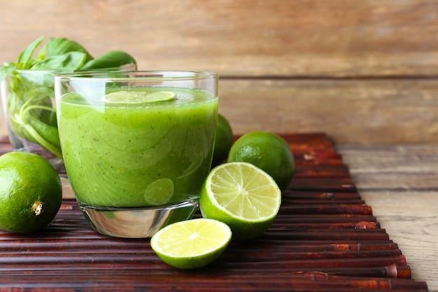 テーブルの上のバジルとライムと緑の健康ジュースのガラスをクローズアップ