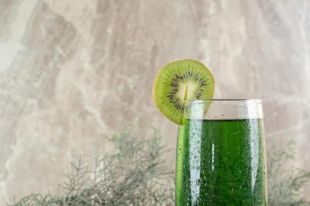 키위 슬라이스와 소나무 가지와 녹색 주스의 유리