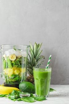 건강 음료를 만들기위한 믹서기에 신선한 육즙 재료와 녹색 스무디 해독의 유리. 채식 요리 개념 프리미엄 사진