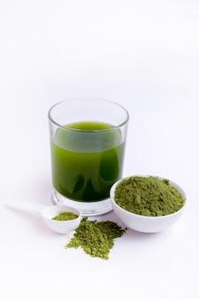 흰색 표면에 녹색 야채 주스와 야채 분말의 유리