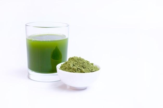 흰색 표면에 그릇에 녹색 야채 주스와 야채 분말의 유리