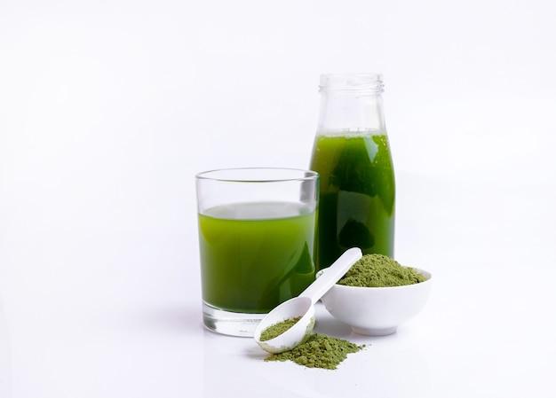 흰색 표면에 숟가락에 녹색 야채 주스와 야채 분말의 유리