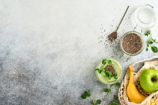 Стакан здорового зеленого смузи и ингредиенты для смузи, свежий шпинат, семена чиа, микрозелень гороха, банан, киви и яблоко в многоразовых сумках для покупок на светло-сером бетонном фоне. вид сверху.