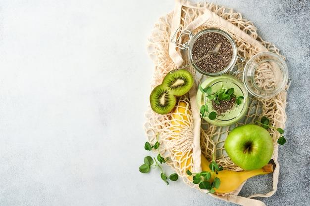健康的なグリーンスムージーのガラスとスムージー、新鮮なほうれん草、エンドウ豆のマイクログリーン、バナナ、キウイ、リンゴ、チアシードの材料をライトグレーのコンクリートの背景に。健康的な食事の飲み物。上面図。