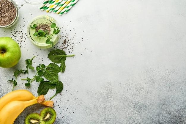 Стакан здорового зеленого смузи и ингредиенты для смузи, свежий шпинат, микрозелень гороха, банан, киви, яблоко и семена чиа на светло-сером бетонном фоне. здоровые пищевые напитки. вид сверху.