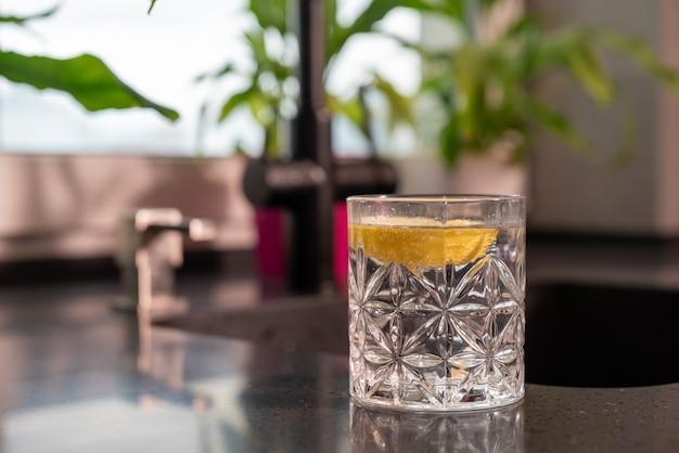 Стакан здоровой чистой пресной воды с пикантным лимоном на столешнице на кухне под низким углом крупным планом, сбоку