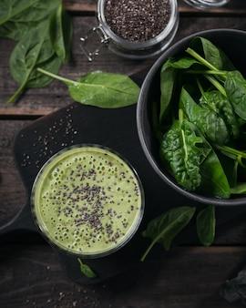 어두운 나무 배경에 신선한 아기 시금치와 치아 씨를 넣은 홈메이드 건강한 녹색 스무디 한 잔. 음식과 음료, 다이어트 및 건강한 식생활 개념
