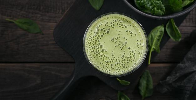 어두운 배경에 신선한 아기 시금치를 넣은 집에서 만든 건강한 녹색 스무디 한 잔. 음식과 음료, 다이어트 및 건강한 식생활 개념