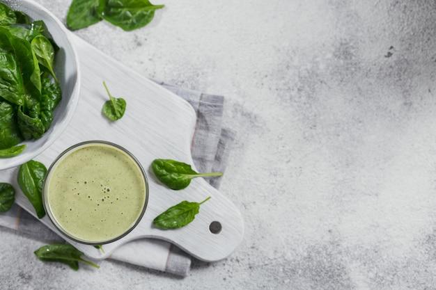 밝은 배경에 신선한 아기 시금치를 넣은 집에서 만든 건강한 녹색 스무디 한 잔. 음식과 음료, 다이어트 및 건강한 식생활 개념