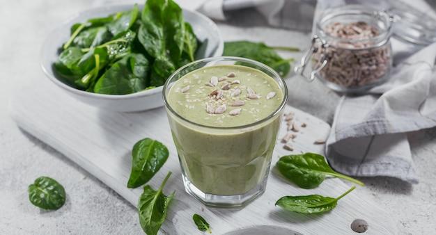 밝은 배경에 신선한 아기 시금치, 해바라기, 참깨를 넣은 홈메이드 건강한 녹색 스무디 한 잔. 음식과 음료, 다이어트 및 건강한 식생활 개념
